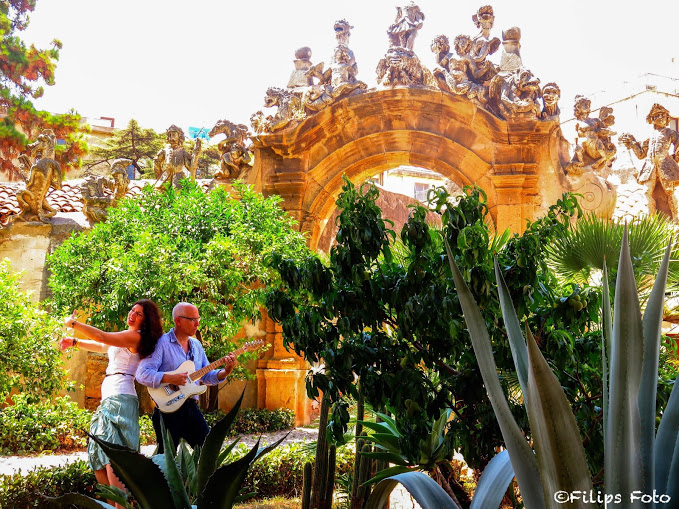 """Allison Scola with husband Joe Ravo as the music duo Villa Palagonia at the estate of Villa Palagonia in Bagheria, Sicily. Photos taken Allison's cousin, Filippo Buttitta. Villa Palagonia is steps from where Allison's grandmother grew up and where her cousins continue to live. A series of musician statues and their various ethnic instruments line the outer walls of the storied estate. Villa Palagonia represents a center of culture and intrigue: in the 18th century, the seventh Prince of Palagonia wanted to provoke visitors emotionally with his """"Villa of the Monsters."""""""